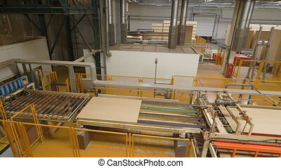 Man or worker controls manufacture or production of fiberboard, particleboard. Production line, workshop or conveyor for the manufacture of wood products