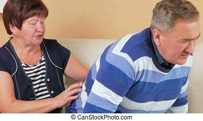man, oud, tries, om te arriveren, op, van, de, bankstel, en, daar, is, een, scherp, pijn, in, zijn, back., vrouw, echtgenoot, massages, de, lagere rug, en, informatietechnologie, wordt, niet, zo, pijnlijk