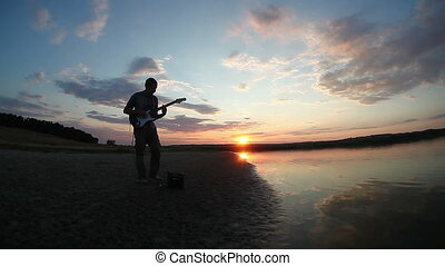 man outdoors at sunset near the lake plays the electric guitar evening sun sets Video