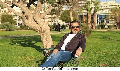 Man outdoors in park smoking