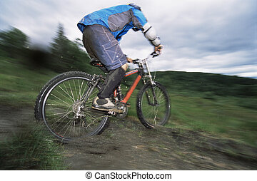 Man outdoors on trails riding bicycle (selective focus)