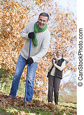 Man outdoors raking leaves and woman in background smiling (selective focus)