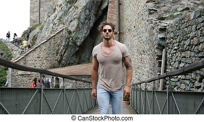 Man outside ancient abbey in Italy - Handsome man walking...