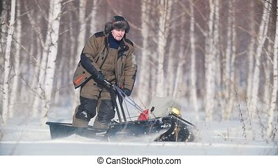 Man overcoming deep snow on a mini snowmobile in the snowy forest, skillful maneuvering
