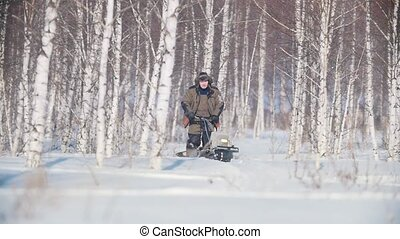 Man overcoming deep snow on a mini snowmobile in the snowy forest