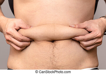 Man overweight pinches the excess fat that he has around his...