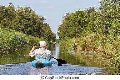 Man paddling in a blue kayak