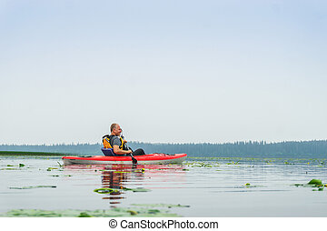 Man paddling kayak among lily flowers on the lake