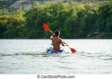 Man Paddling Kayak on Beautiful River or Lake at the Evening