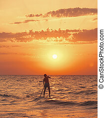 Man paddling on a SUP board in the sea at sunset.