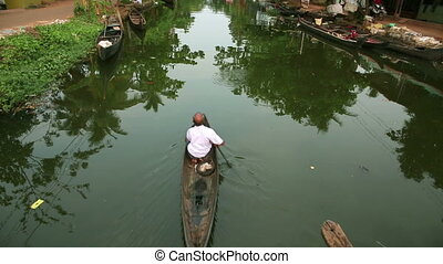 Man paddling on canal - Local man paddling on canal in...