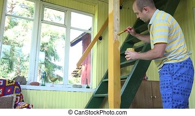 man paint yellow colour wooden column near stairs to loft. 4K