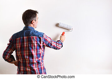Man painting a wall of his house in white