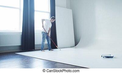 Man painting cyclorama in photo studio using roller painter ...