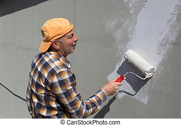 Man painting facade with roller