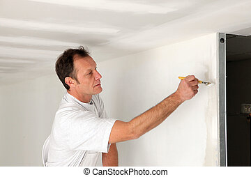 Man painting final touches to wall
