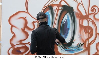Man painting graffiti - Back view of graffiti artist...