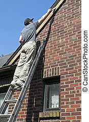 Man painting house trim - Man stretching to paint primer on...