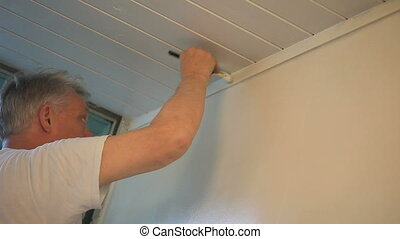 a man paints the upper portion of an inside wall