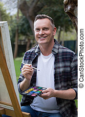 Man painting on canvas in garden