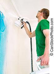 Man painting walls using spray gun