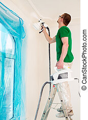 Man painting walls with paint spray gun