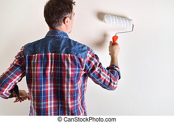 Man painting with roller a white wall behind detail