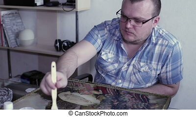 Man paints a picture with varnish - A man sits at a table...