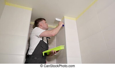 Worker painting ceiling with white paint. Painter man paints bathroom ceiling with roller tool. Handyman type using paint roller. Repair in apartment. Homeowner making renovation repair at home.