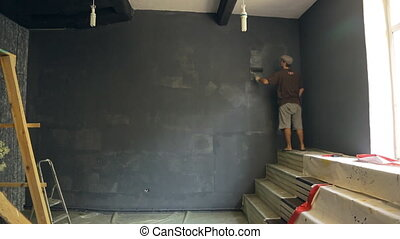 Man paints wall for photo studio in a grey background with a roller, standing on stairs, near window.