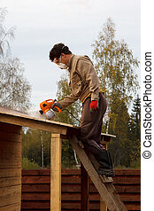 man paints wooden shelter with spray gun