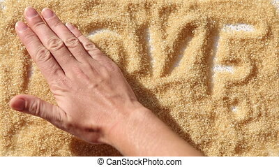 man palm smooth word LOVE on brown sugar surface