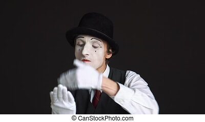 man pantomime talking on an imaginary cell phone and swears on a black background