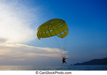 Man parasailing at sunset