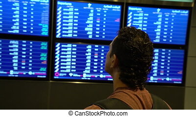 man passenger looking at timetable board screen at the airport terminal, international flight, business man travels abroad concept