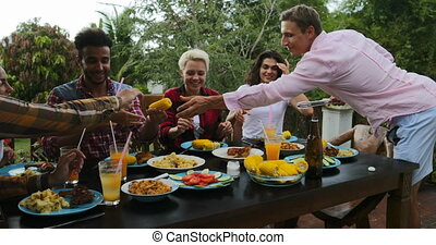 Man Passing Food To People Sitting At Table Eating Young...