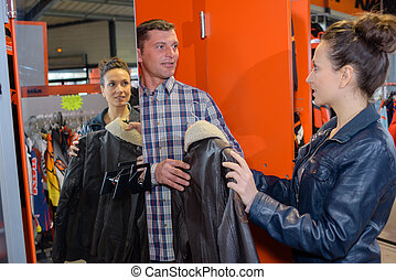 man passing leather jacket to woman in shop
