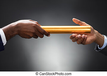 Man Passing The Golden Baton To His Partner