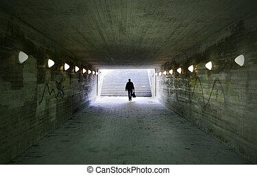 man passing through underpass - shadowy man passing through...