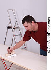 Man pasting wallpaper