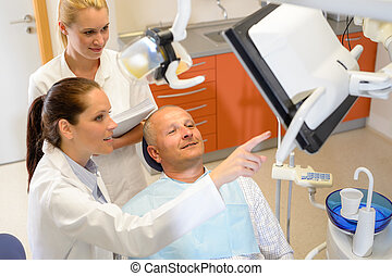 Man patient at dental consultation dentist surgery -...