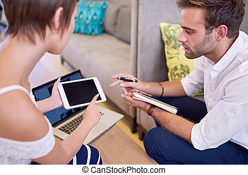 Man paying attention to tablet being held by woman