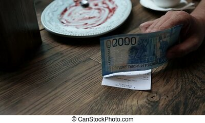 Man paying cash for bill in cafe. Paper money banknotes in...