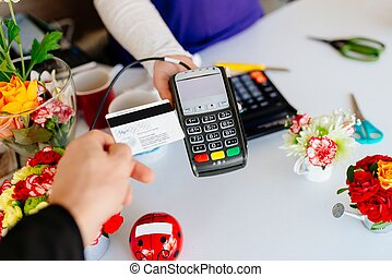 Man paying for flowers with his debit card.