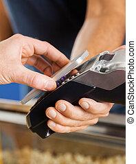 Man Paying Through NFC Technology At Cinema