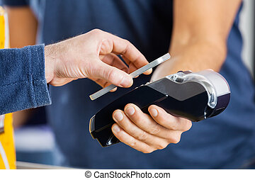 Man Paying Through NFC Technology At Cinema - Cropped image...