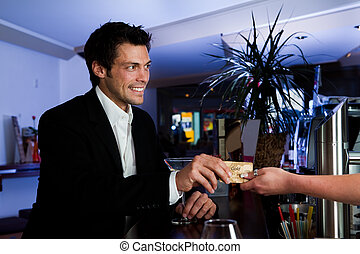 Man paying with credit card - Man at the bar paying with...