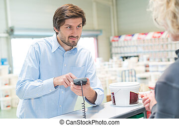 man pays in hardware store