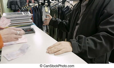 Man pays money in cash in the clothing store shop