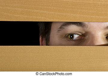 Man peeks through the blinds - A man glances through the...